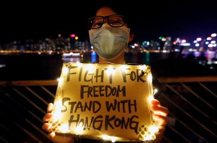 Hong Kong, August 23, 2019. A woman holds up a sign while, along Tsim Sha Tsui ...