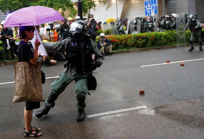 An anti-riot police officer approaches a protestor at a rally ...
