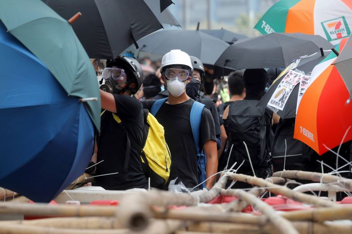A protester stands near a barricade made of bamboo stems at a protest ...