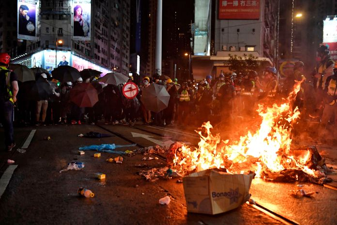 Protesters stand near burning items during a protest on Hennessy Road, Hong Kong on August 31, 2019, ...
