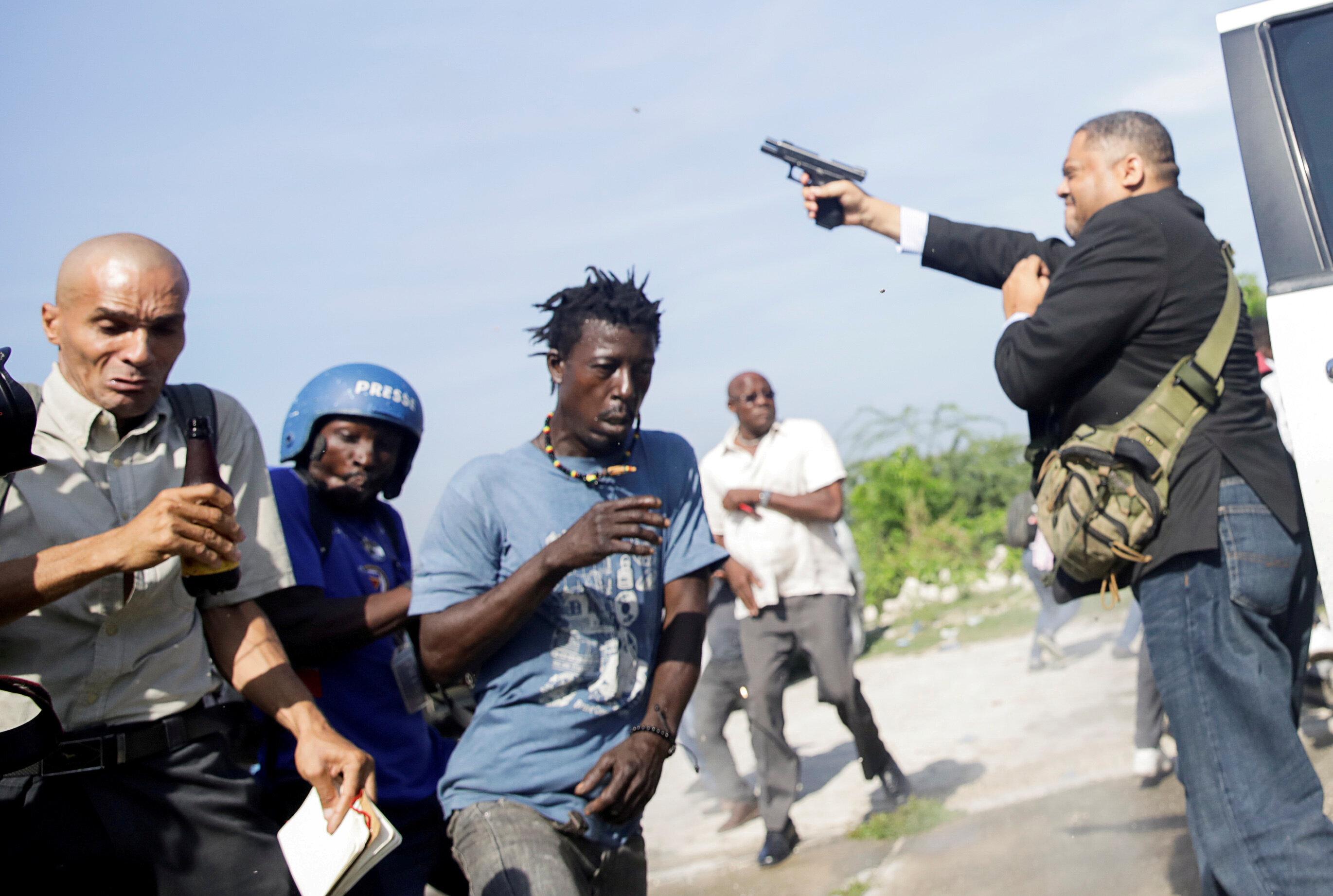 People run as Haiti's Senator Jean Marie Ralph Fethiere (PHTK) fires a gun in the air, injuring Chery Dieu-Nalio, a photograp