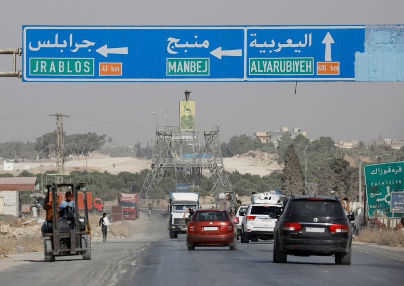 Cars pass under a road sign that shows the direction to Manbij city, at the entrance of Manbij, Syria October 15, 2019. REUTERS/Omar Sanadiki