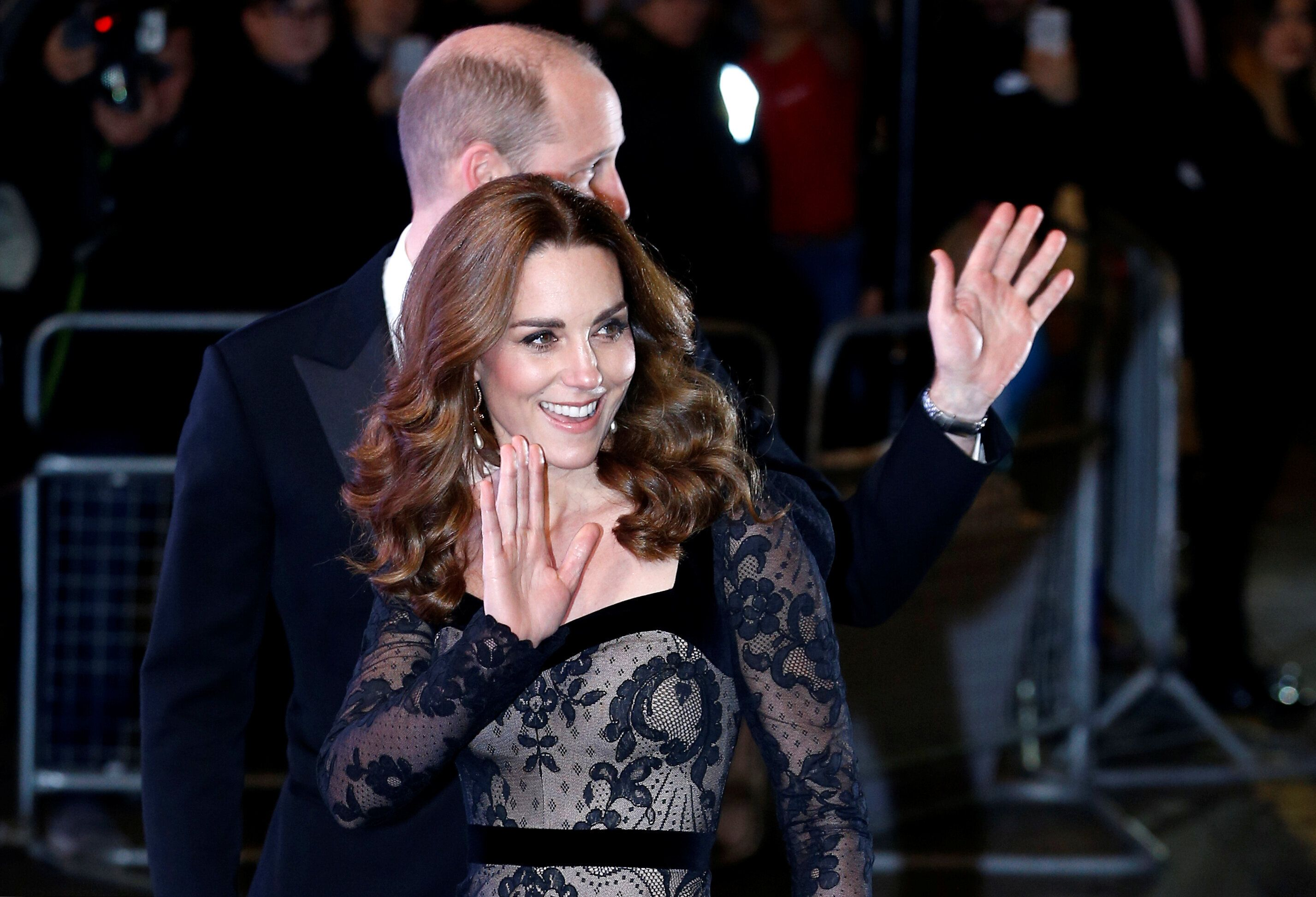 The royals are pictured waving to the crowds as they walked into the theater.