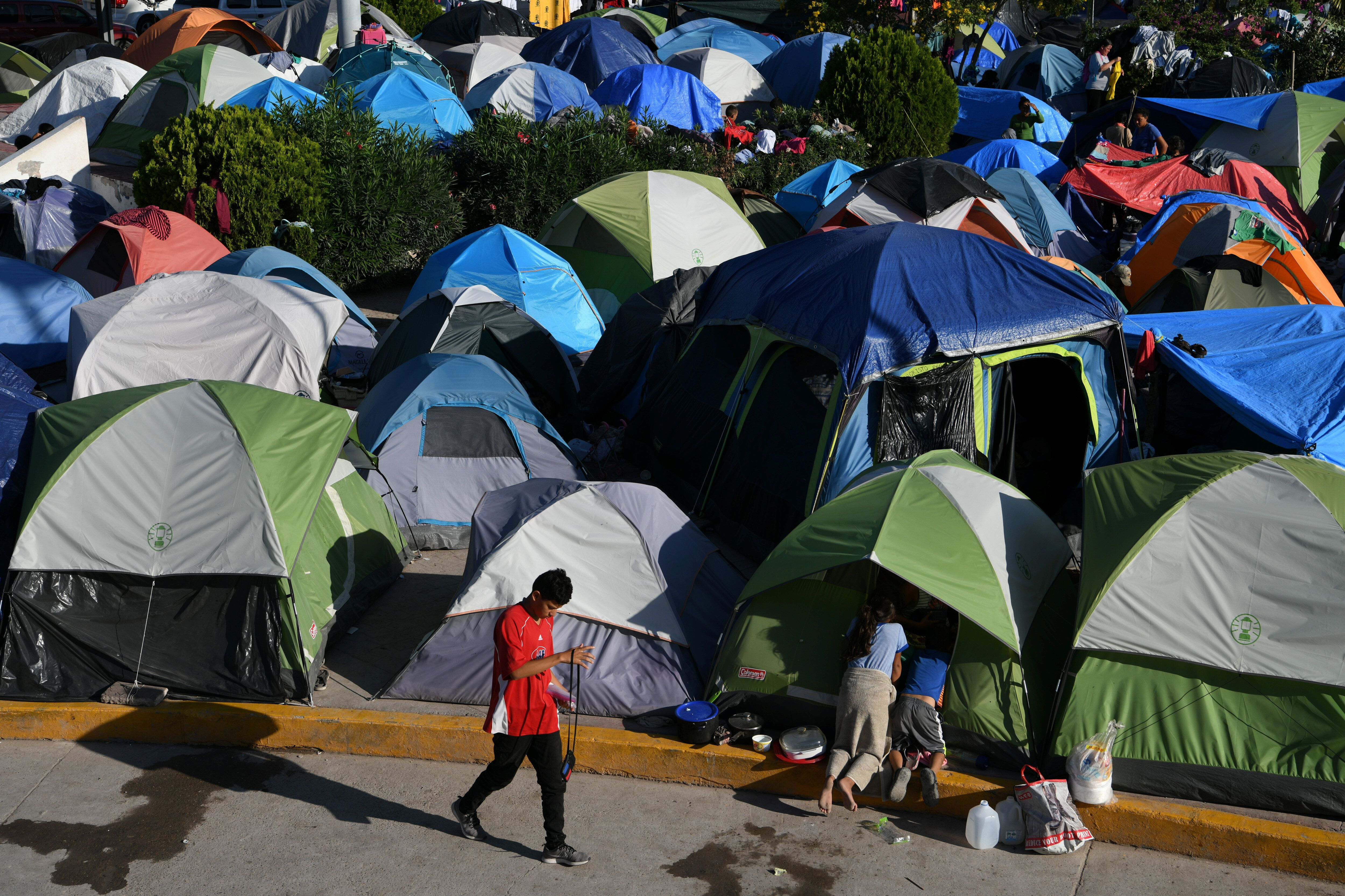 """Migrants, most of them asylum-seekers sent back to Mexico from the U.S. under the """"Remain in Mexico"""" program, occupy a makesh"""