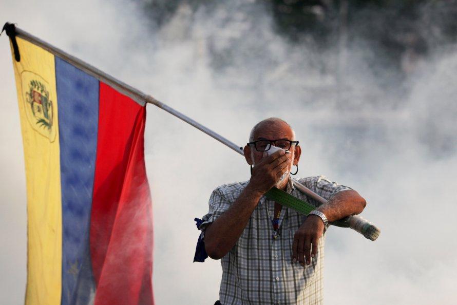 Un oponente de Maduro que lleva una bandera venezolana se cubre la cara contra el gas lacrimógeno disparado durante un intento de levantamiento militar para derrocar al presidente el 30 de abril de 2019.