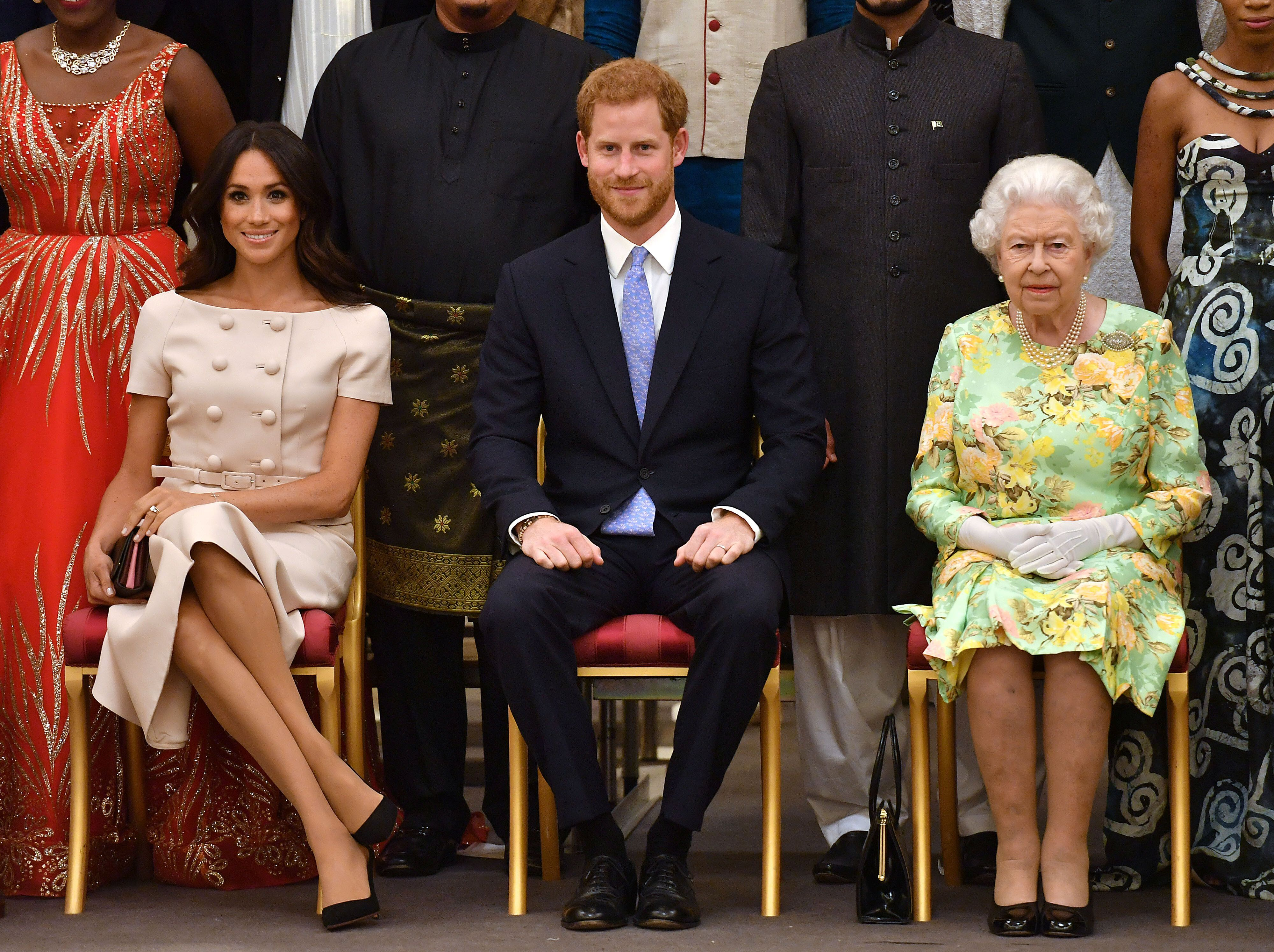 Queen Elizabeth, Prince Harry and the Duchess of Sussex pose for a picture with some of Queen's Young Leaders at a Buckingham