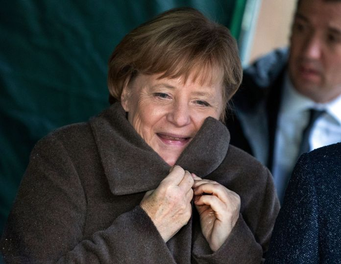 German Chancellor Angela Merkel adjusts her coat on a site of the laying of foundation stone for a new ...