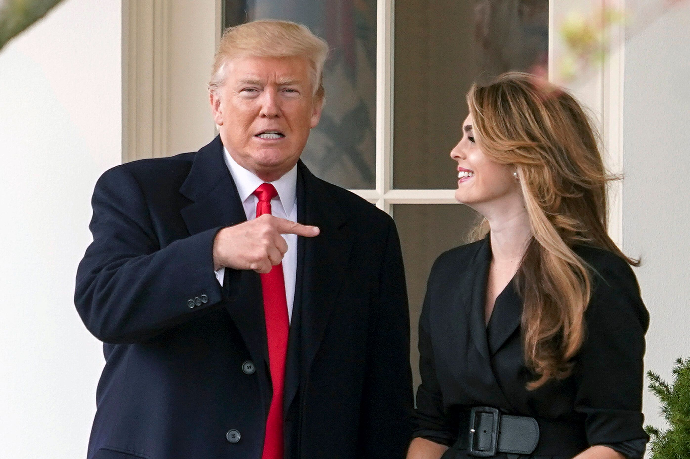 President Donald Trump points to outgoing White House communications director Hope Hicks on her last day before he boards Mar