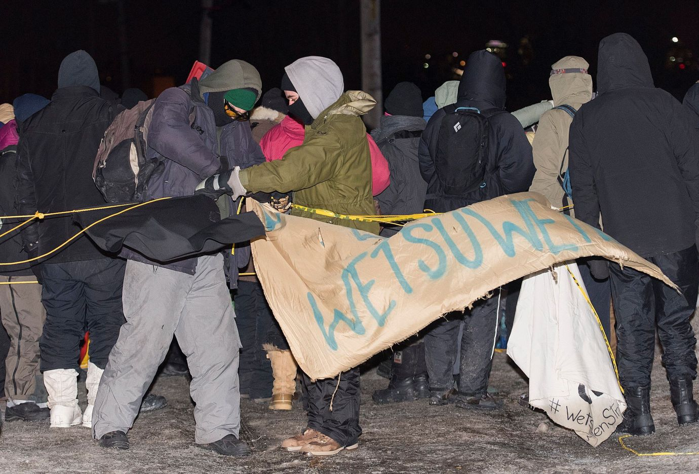 Protesters remove a sign as they leave rail blockade in Saint-Lambert, Que. on Friday.