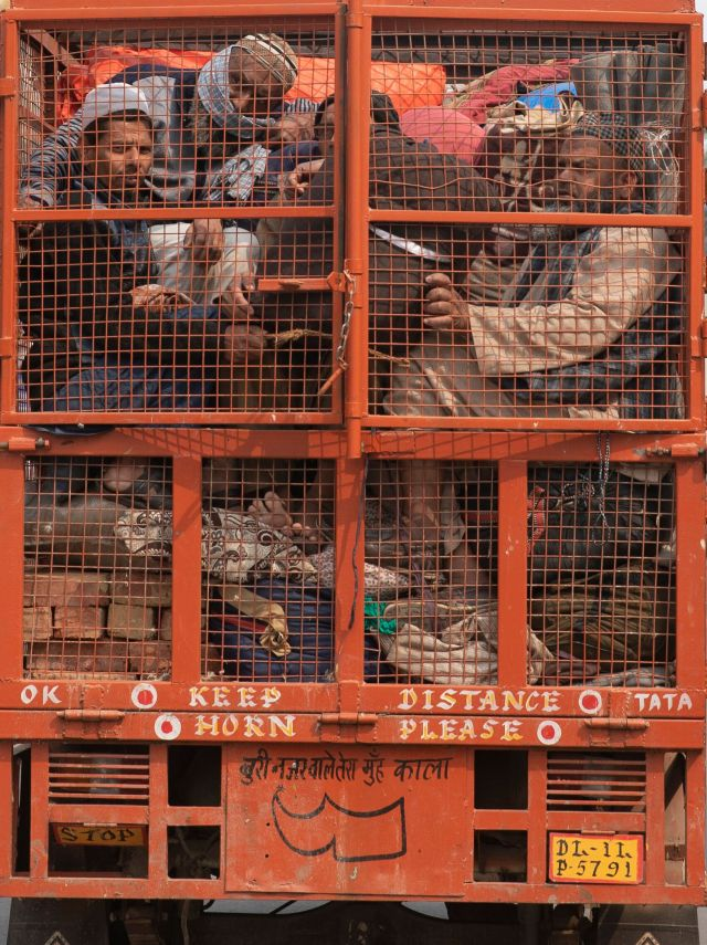 A group of Muslims huddle together in the back of a mini truck and leave the area after Tuesday's violence in New Delhi.
