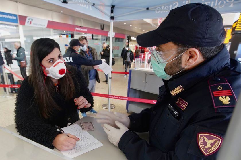 A traveler wears a mask as she fills out a form at a check point set up by border police inside Rome's Termini train station,