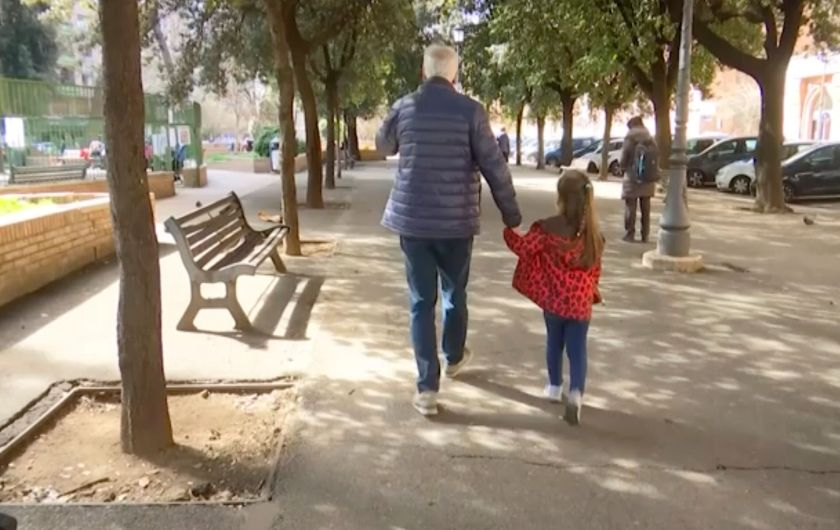 A young girl walk with her elderly grandparent along a tree lined avenue in Rome, Italy, Thursday March 5, 2020, after the It