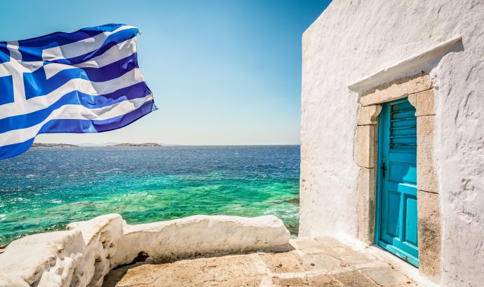 Bright and colorful image of Greek National Flag on Mykonos Island. White building with blue door at...