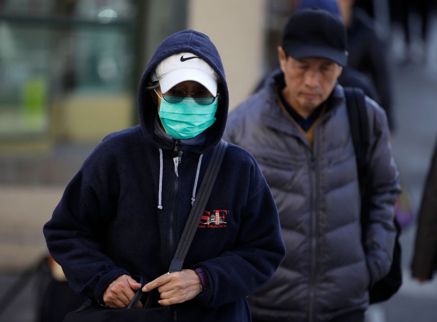 A masked woman walks a street in the Chinatown district of San Francisco on Jan. 31. Chinese Americans in California have enc