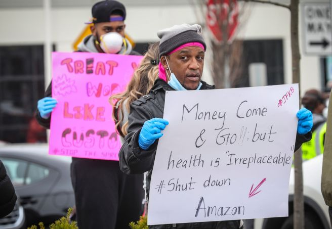 Gerald Bryson, left, join workers at an Amazon fulfillment center in Staten Island, New York, protesting conditions in the co