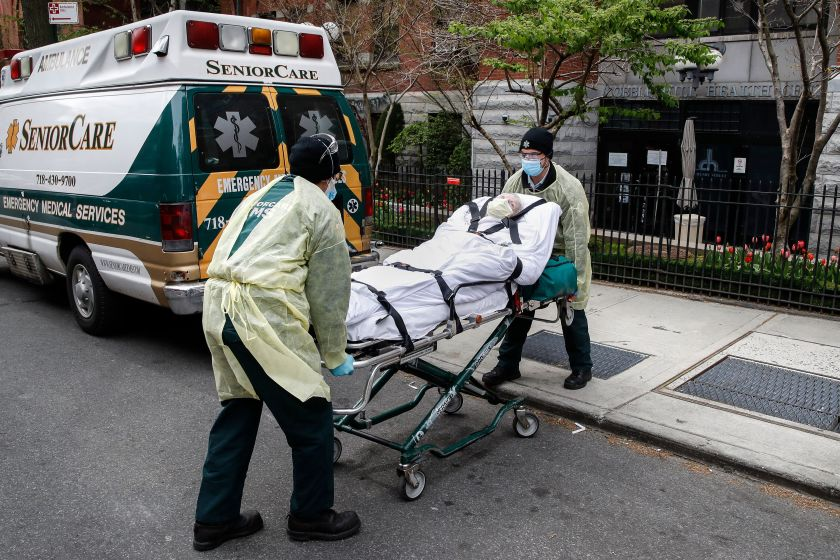 A patient is loaded into the back of an ambulance by emergency medical workers outside Cobble Hill Health Center, Friday, Apr