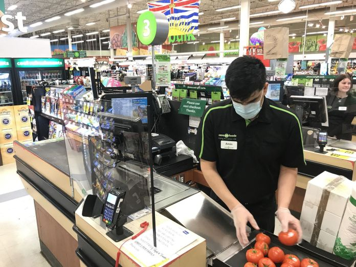 A plexiglass barrier is shown creating a barrier to protect a cashier in a grocery store in the North ...