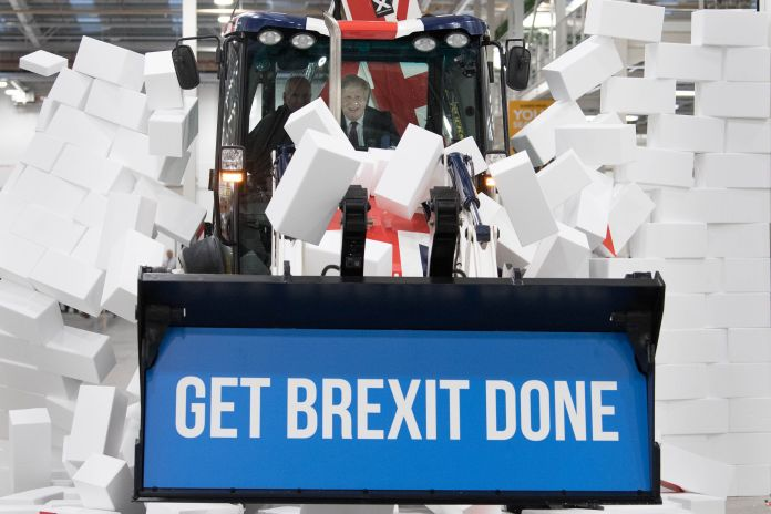 "Johnson driving a Union flag-themed JCB, with the words ""Get Brexit Done"" inside the digger bucket, through a fake wall embla"