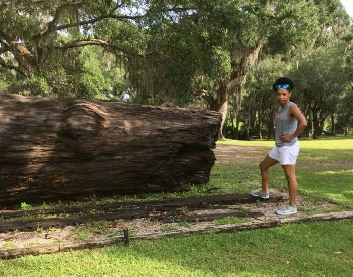 The author standing next to a log that slaves cut down at a South Carolina rice plantation.