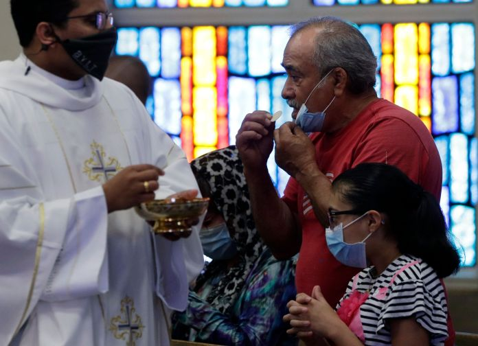 The Rev. Praveen Lakkisettit, left, wears a face mask as he delivers communion to parishioners during an in-person Mass at Ch
