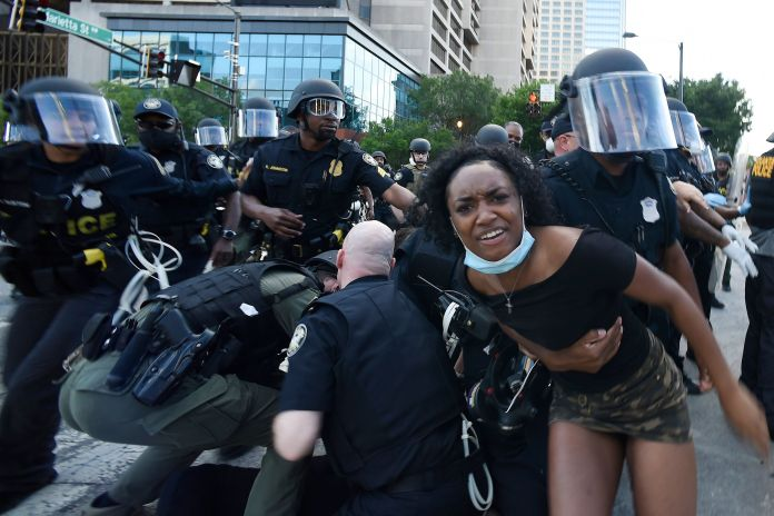 Police detain demonstrators protesting in Atlanta on Saturday. The protest started peacefully earlier in the day before demon