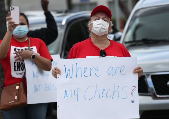Protesters stand together demanding that the state of Florida fix its unemployment system on May 22 in Miami Beach, Florida.