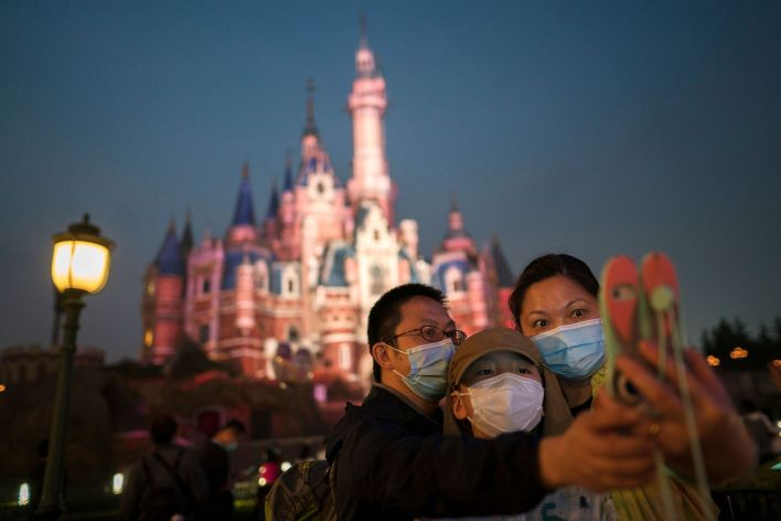 Masked people visit Shanghai Disneyland after its reopening on May 11, 2020.