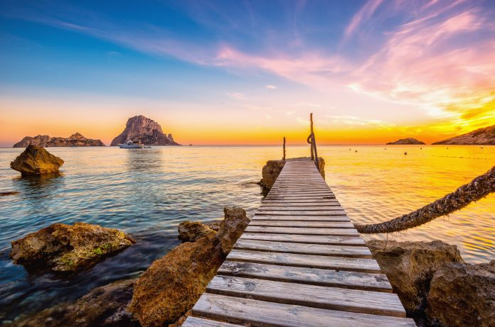 Sunset and boat at the beautiful beach of Cala D'hort, in Ibiza (Spain)