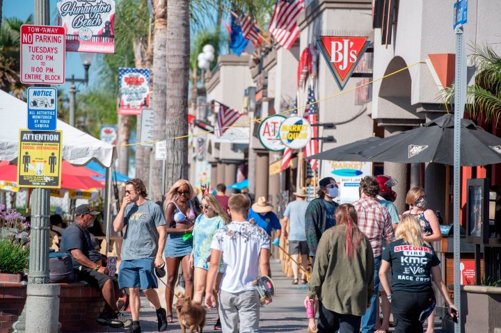 """Beachgoers, many maskless, walk down Main Street in Huntington Beach, California. Residents of the city south of Los Angeles have been notably&nbsp;<a href=""""https://www.latimes.com/socal/daily-pilot/news/story/2020-06-30/huntington-beach-restaurants-no-mask-position-deeply-divides-o-c-diners"""" target=""""_blank"""" rel=""""noopener noreferrer"""" data-ylk=""""subsec:paragraph;itc:0;cpos:1;pos:3;elm:context_link"""" data-rapid_p=""""3"""" data-v9y=""""1"""">anti-mask</a>&nbsp;and <a href=""""https://timesofsandiego.com/politics/2020/05/01/thousands-many-without-masks-protest-lockdown-in-huntington-beach/"""" target=""""_blank"""" rel=""""noopener noreferrer"""" data-ylk=""""subsec:paragraph;itc:0;cpos:1;pos:4;elm:context_link"""" data-rapid_p=""""4"""" data-v9y=""""1"""">lockdown-averse,</a>&nbsp;in spite of rising coronavirus cases in the region."""
