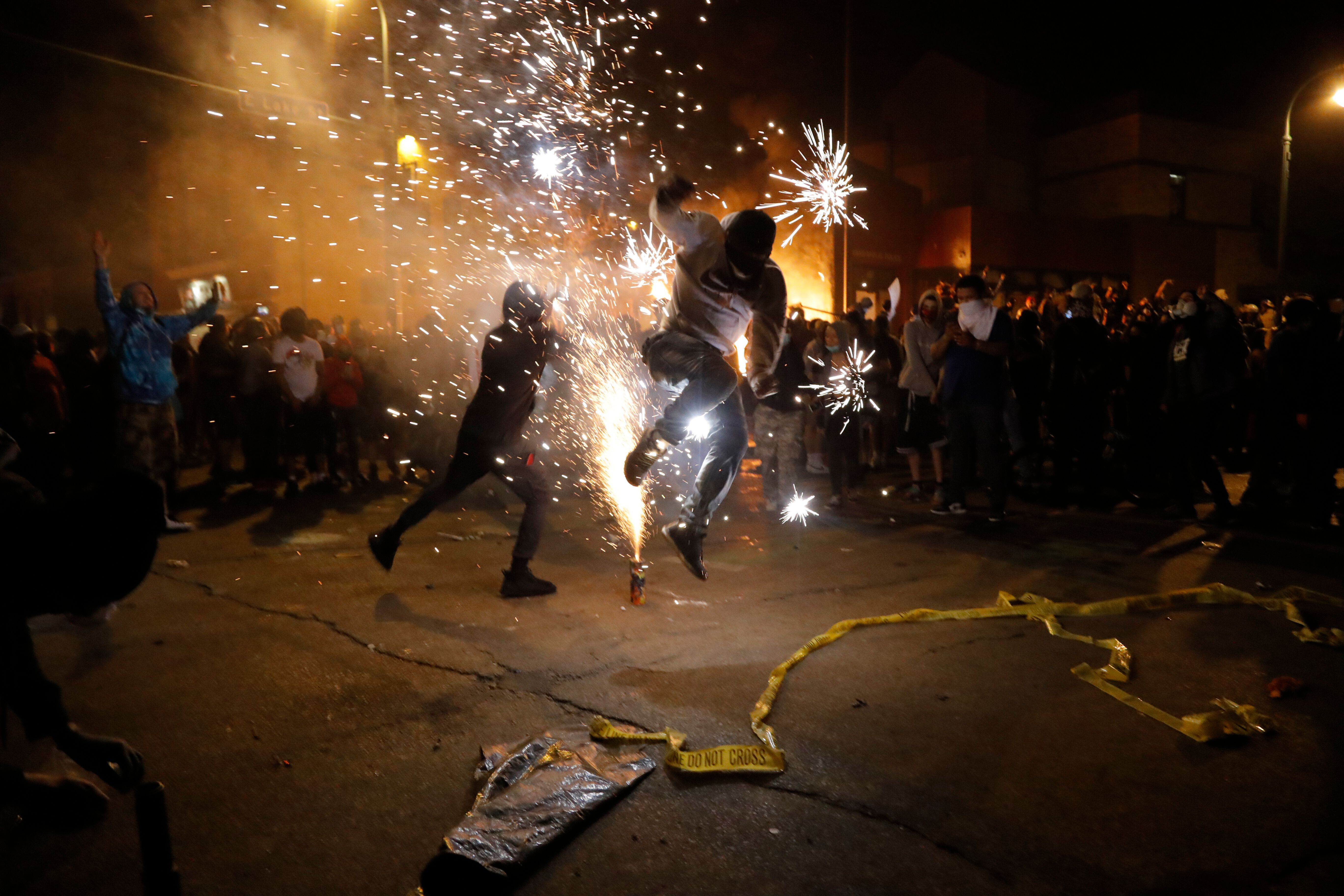 Protesters set off fireworks as a fire burns at the Minneapolis police 3rd Precinct building, May 28, following the police ki