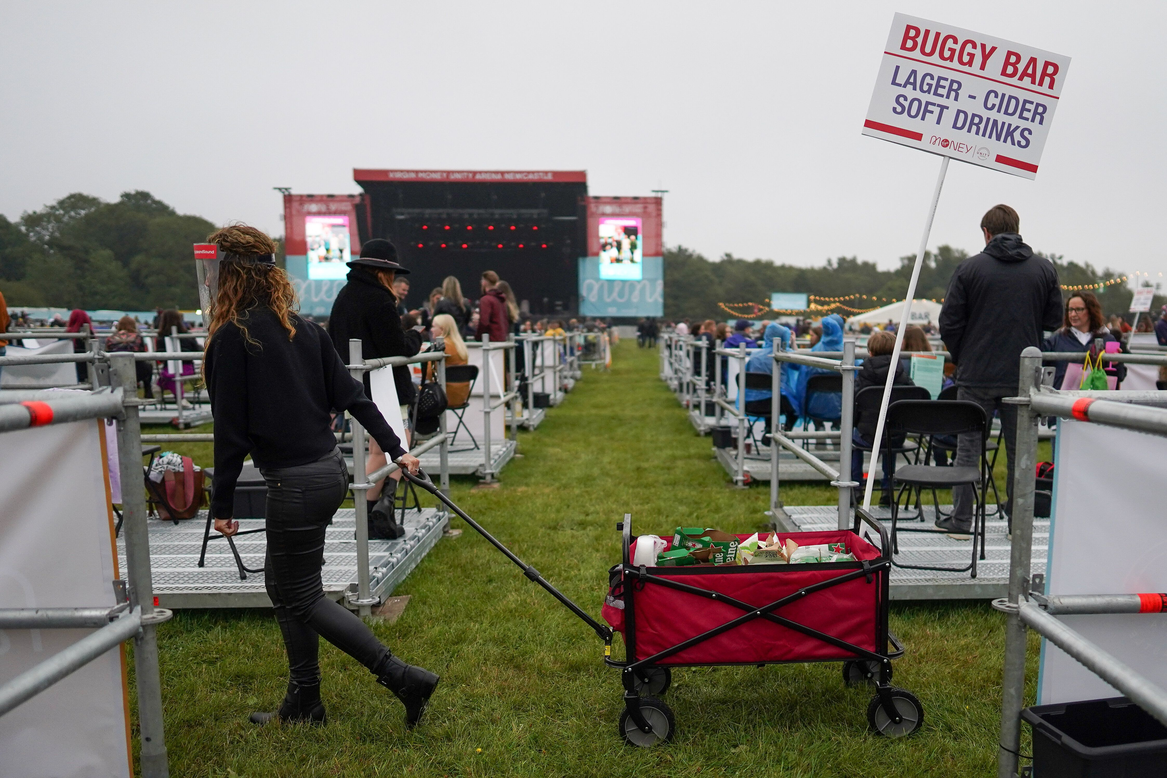An employee wheels a mobile drink trolley between socially distanced enclosures ahead of Sam Fender performing at the Virgin