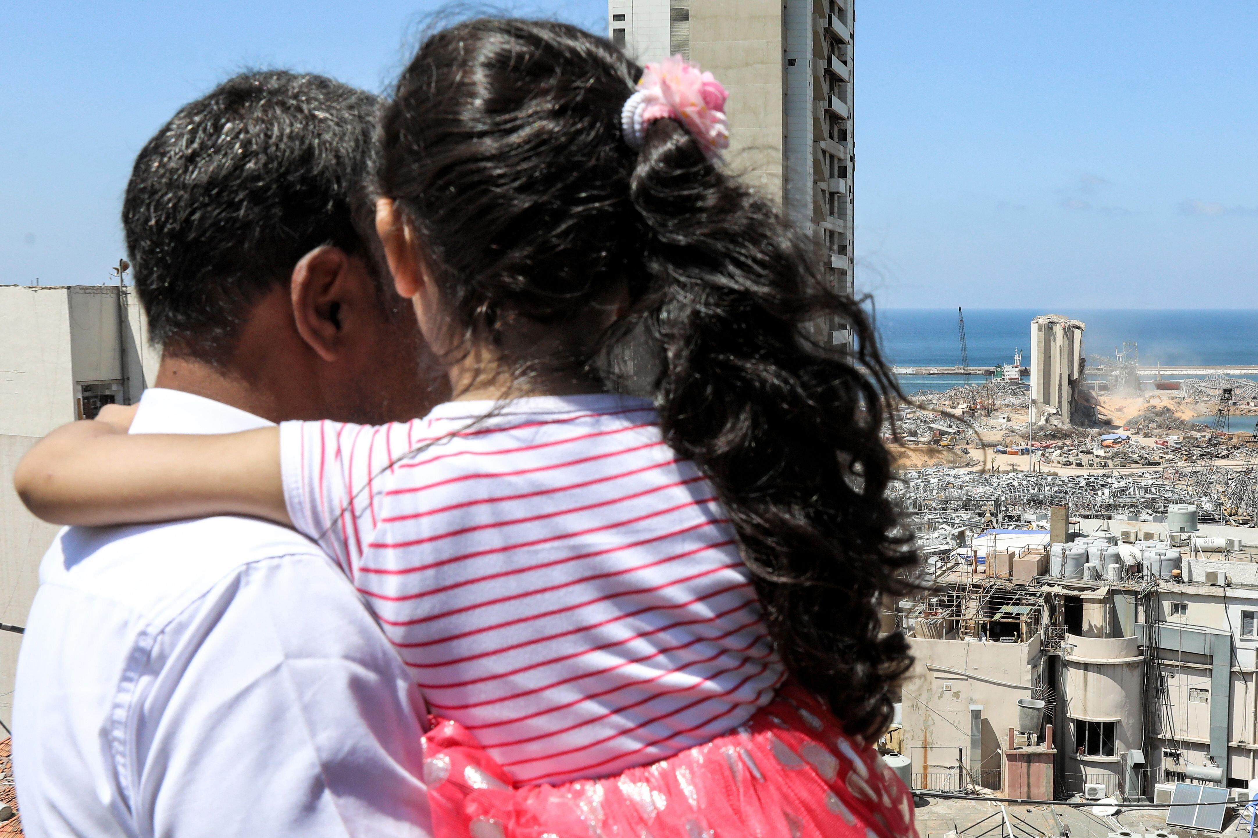Makhoul Mohammad al-Hamad, 43 ans, regarde depuis son appartement le port détruit avec dans ses bras...