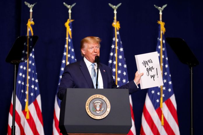 """Trump holds a sign that reads, """"Never give up!"""" as he speaks to evangelical supporters in Miami on Jan. 3, 2020."""