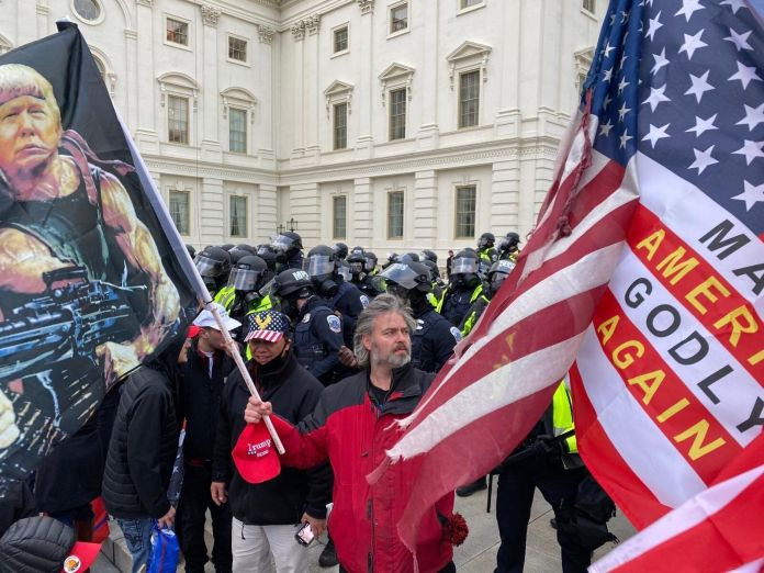"""A man carries a flag with the words """"Make America Godly Again"""" during an insurrection at the U.S. Capitol building in Washing"""
