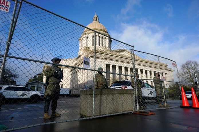 Washington National Guard members stand watch along a perimeter fence, Sunday, Jan. 17, 2021, at the Capitol in Olympia, Wash