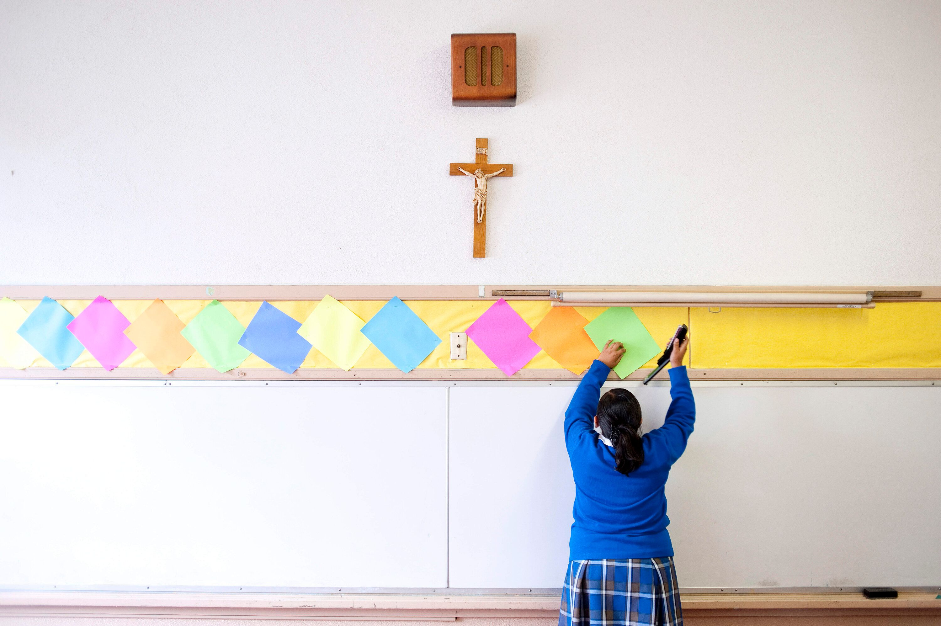 A photo from July 2012 shows a student stapling colored paper to the wall of a classroom at Our Lady of Lourdes in Los Angele