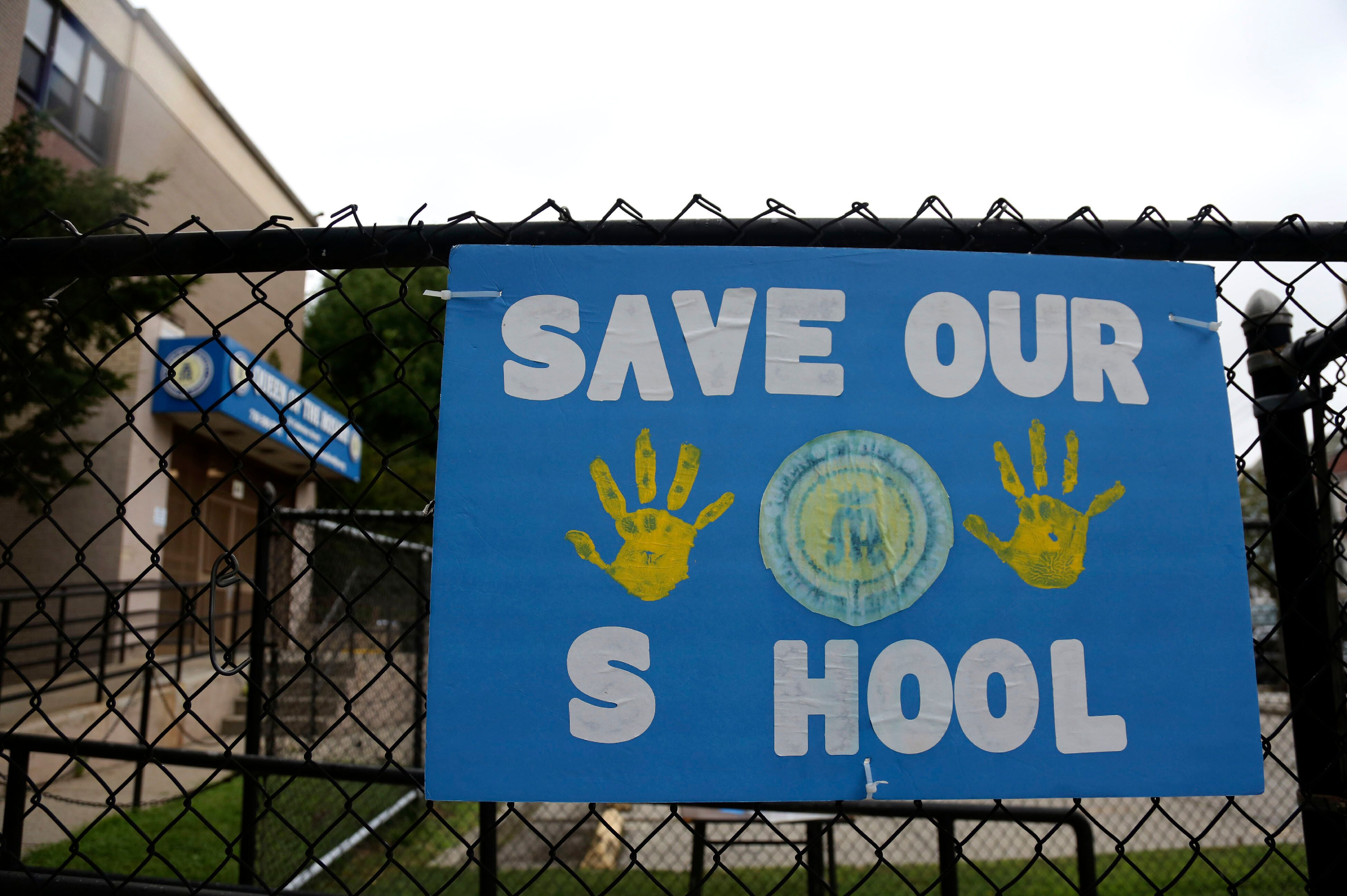 A sign made by parents and students of Queen of the Rosary Catholic Academy hangs on the fence outside the school in Brooklyn