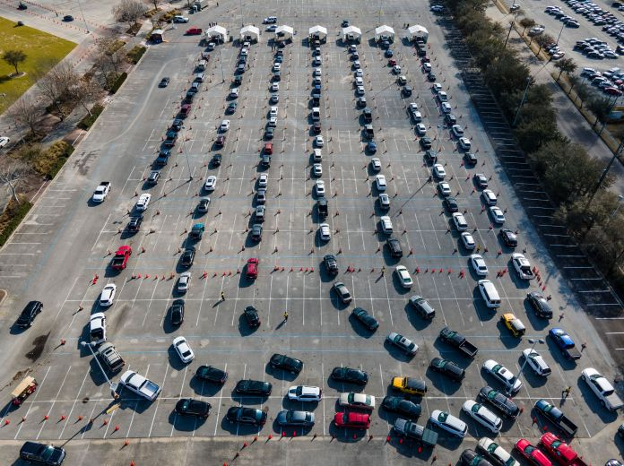 Cars line up in a parking lot at NRG Park in Houston as people wait to receive a COVID-19 vaccines at the federally supported