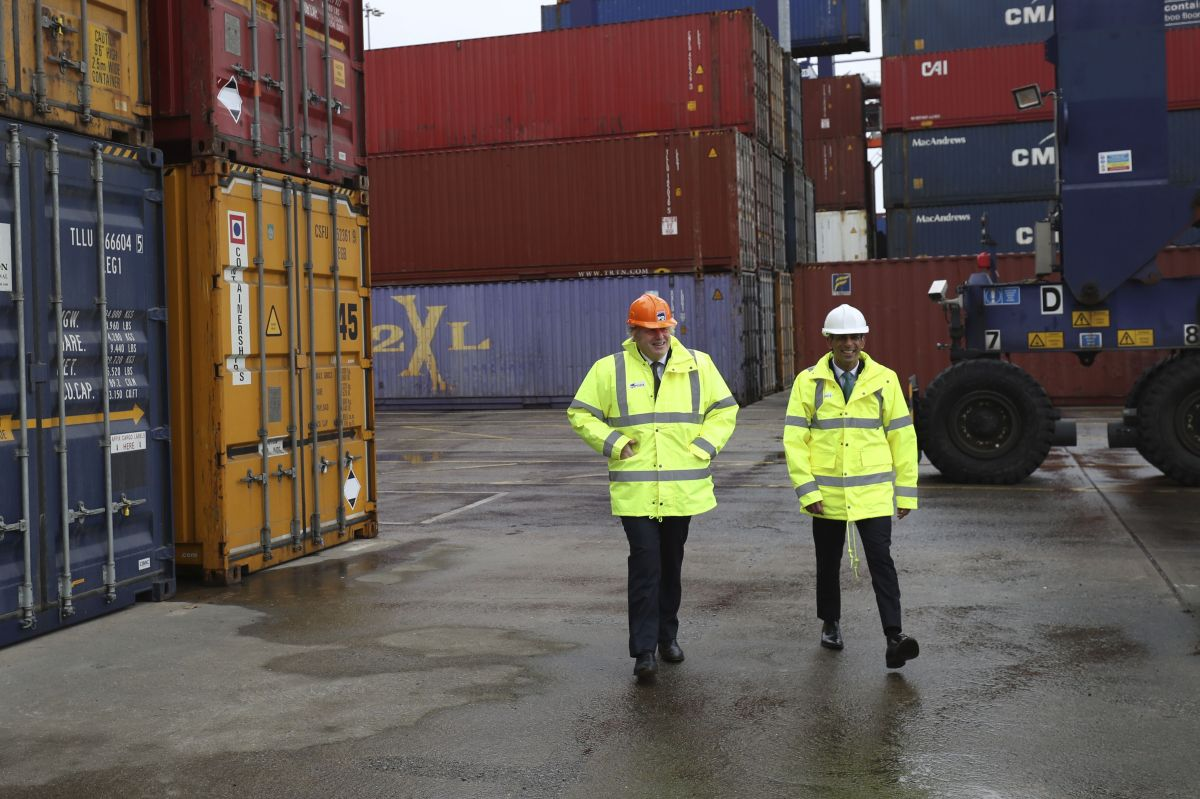 Boris Johnson and Rishi Sunak walk past shipping containers during a visit to