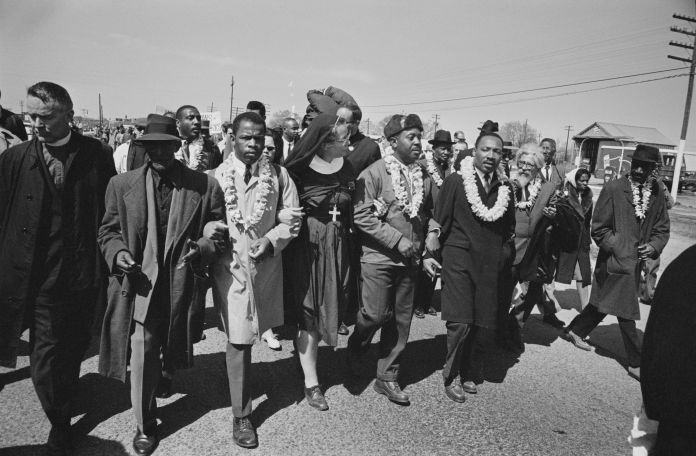 The Rev. Martin Luther King Jr., arm in arm with the Rev. Ralph Abernathy, leads marchers as they begin the march from Brown'