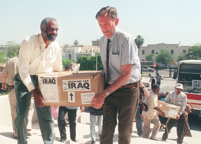 Former US attorney general Ramsey Clark is carrying boxes full of medicines in Baghdad. Clark arrived a day earlier with a mu