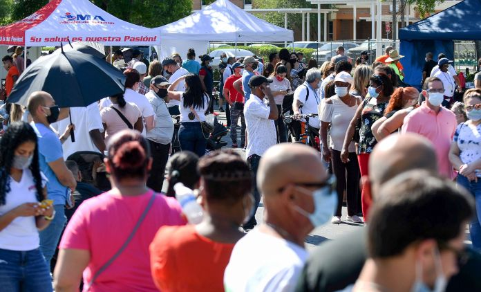 People wait in line for hours on April 9, 2021, at a pop-up COVID-19 vaccination site in the parking lot of Bravo Supermarket