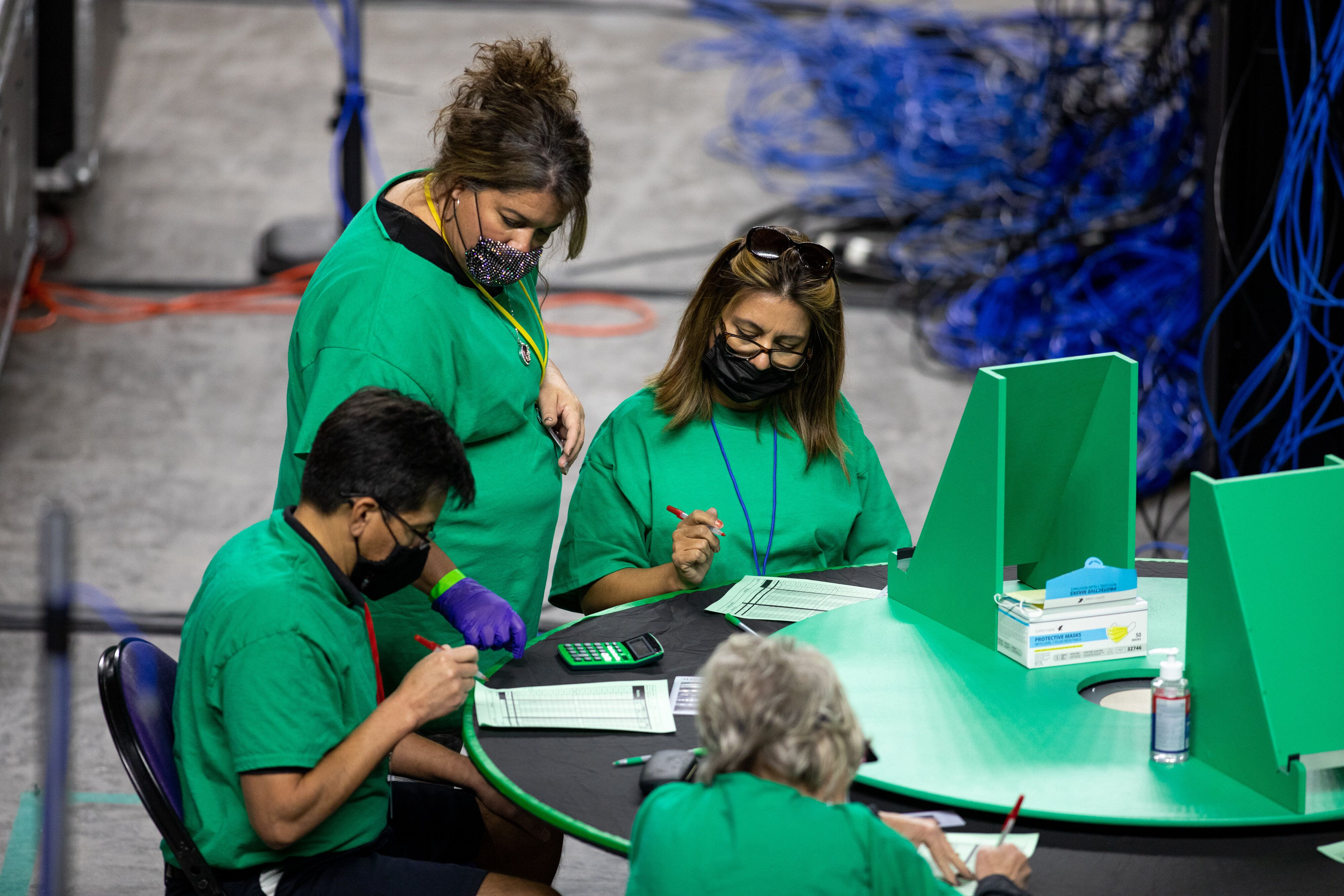 Contractors working for Cyber Ninjas, which was hired by the Arizona state Senate, examine and recount ballots from the 2020
