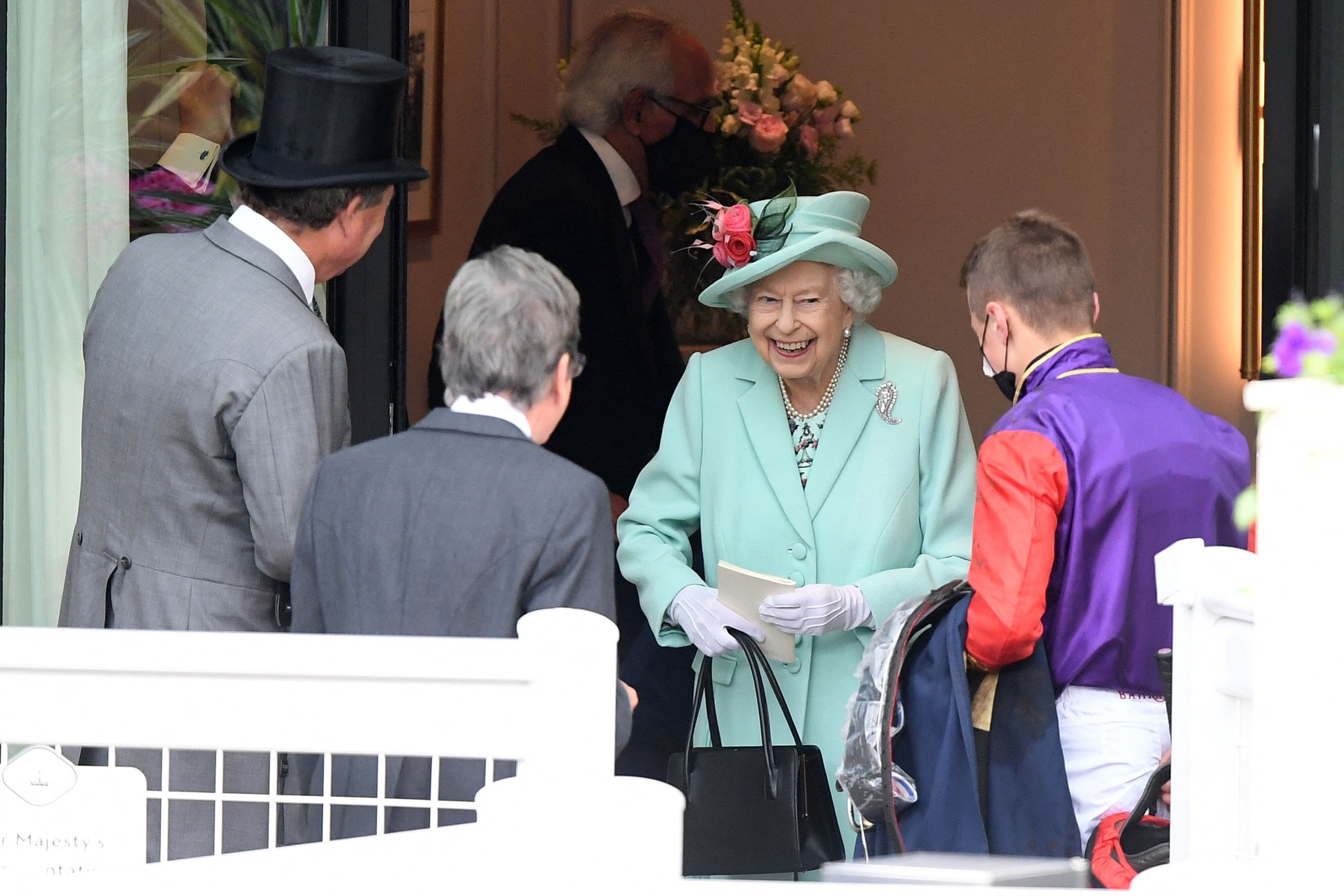 The queen smiles as she meets a jockey on the fifth day of the Royal Ascot horse racing meet. Royal Ascot reopened its doors