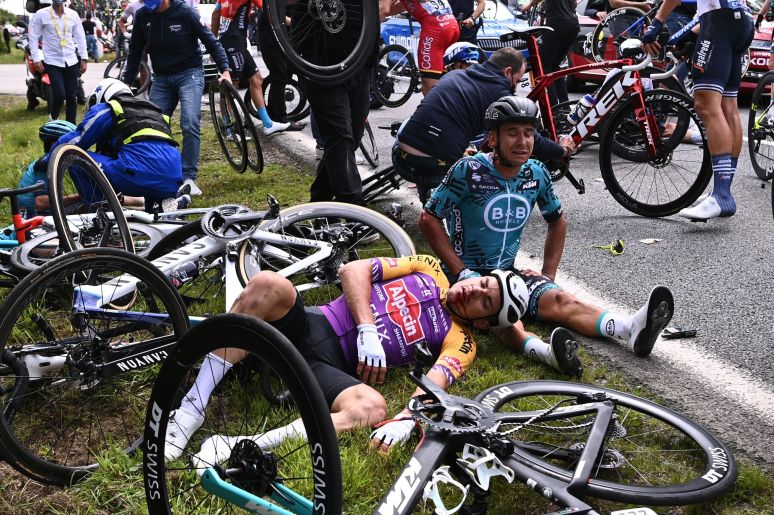 Two cyclists lie on the ground after crashing during the 1st stage of the 108th edition of the Tour de France cycling race on