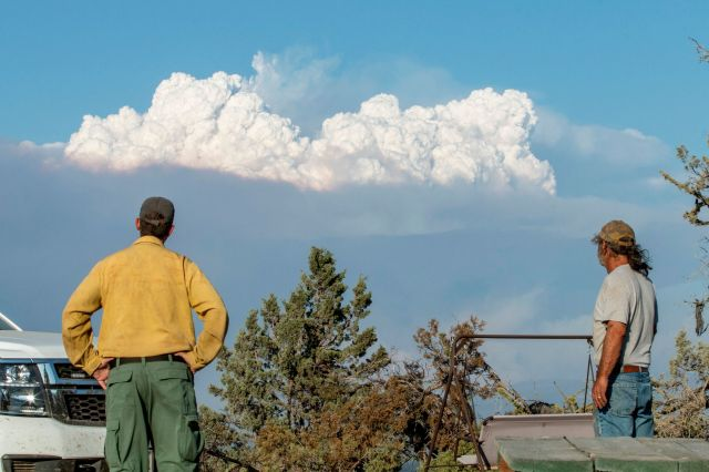 Fire Mitigation and Education Specialist Ryan Berlin (L) and home owner Bob Dillon watch the Bootleg Fire smoke cloud from Di