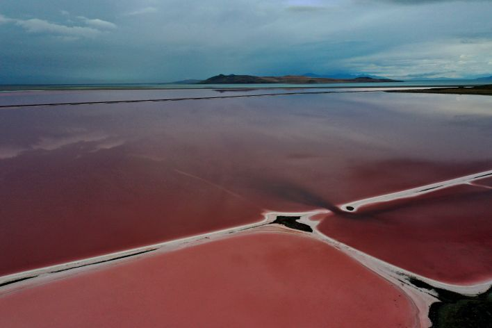 In an aerial view, evaporation ponds that are pinkish-red due to high salinity levels are visible on the north section of the