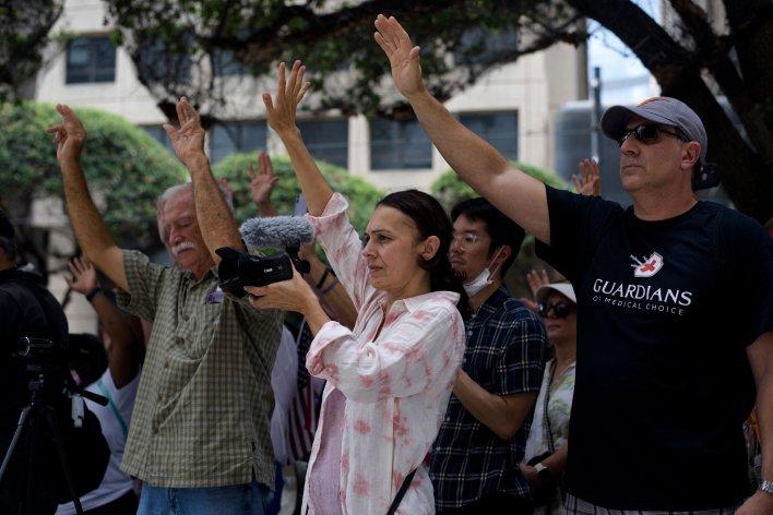 Anti-vaccine protesters pray outside of Houston Methodist Hospital in Houston, Texas, on June 26, 2021. More than 150 hospita