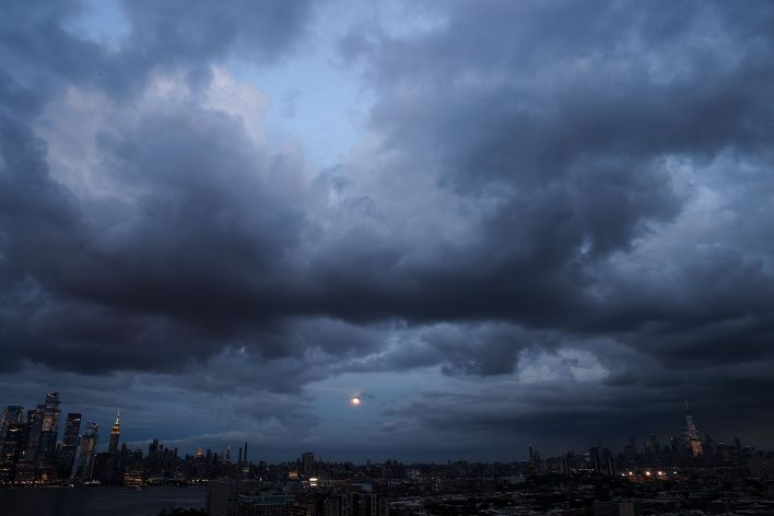 Huge clouds are seen as the full moon rises over Manhattan on August 20, 2021.