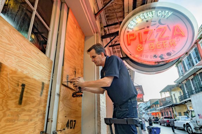 Michael Richard of Creole Cuisine Restaurant Concepts boards up Crescent City Pizza on Bourbon Street in the French Quarter b